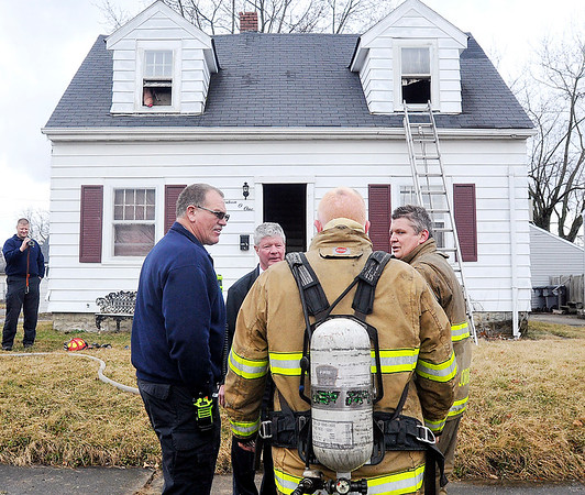 John P. Cleary    The Herald Bulletin<br /> Anderson firefighters gather details after fighting a fire in this two-story house in the 1600 block of Poplar Street Tuesday afternoon. There were no injuries reported.