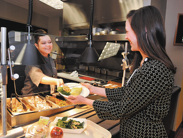 John P. Cleary    The Herald Bulletin<br /> Sarah Loser serves Carrie Scott, a dietitian for St. Vincent Anderson Regional Hospital, a grilled chicken breast to go with other healthy food options that Scott has on her tray from the hospital's cafeteria.
