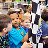 John P. Cleary |  The Herald Bulletin<br /> CRA Super Series race car driver Dalton Armstrong talks to East Elementary School kindergarten students Wednesday about racing. Here students look over a checkered flag as it is passed around the room.