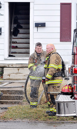 John P. Cleary |  The Herald Bulletin<br /> Anderson firefighters spray each other down as they clean debris off their gear after battling a fire at a house in the 1600 block of Poplar Street Tuesday afternoon.