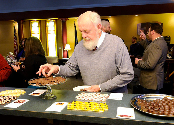 Don Knight | The Herald Bulletin<br /> Ralph Lumm picks out an assortment of chocolates to try during the Anderson Symphony Orchestra's third annual Chocolate and Wine Tasting fundraiser held at the Laura Sandlin Agency on Saturday. The event is a fundraiser for ASO.