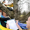 John P. Cleary |  The Herald Bulletin<br /> Anderson University freshmen Levi Vick of Richmond and Vanessa Schuldt of Danville enjoy the warm afternoon from their hammocks in the middle of this tree in front of Rice Hall Tuesday.