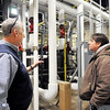 John P. Cleary |  The Herald Bulletin<br /> Steve Vore, assistant to Madison-Grant United School Corp. superintendent, and Stan Davis, head of maintenance for the school corporation, look over one of the areas of the heating system that has been upgraded already.