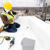 Don Knight | The Herald Bulletin<br /> Alex Zabala cuts a piece of membrane to size as he works on an inside corner of the roof at the Madison County Government Center on Wednesday.