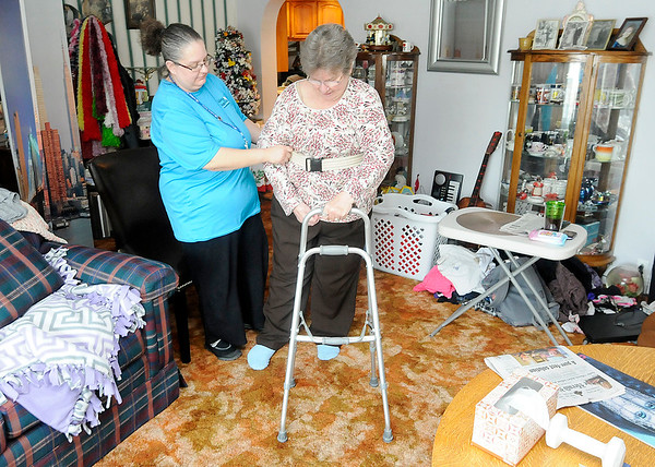 Don Knight | The Herald Bulletin<br /> Heather Majors, a Visiting Angels caregiver, helps Sharon Galbreath walk to her couch at her Frankton home on Friday.