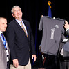 "Don Knight | The Herald Bulletin<br /> Bridges of Hope CEO Carl Waterman, right, surprises Gov. Eric Holcomb with a t-shirt during their grand opening on Saturday. At left is Director of Operations Karl Lazar. The shirt refers to the five pillars in Governor Holcomb's legislative agenda, the fourth of which is to ""attack the drug epidemic."""