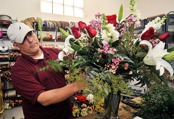 John P. Cleary |  The Herald Bulletin<br /> Toles Flowers floral designer David Schwartz puts the finishing touches on this  arrangement Monday afternoon as the store is swamped with orders to fill and more coming in as they prepare for Valentine's Day.
