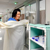 John P. Cleary | The Herald Bulletin<br /> St. Vincent Anderson RN Kay Replogle gets dressed in a sterile gown, mask, and gloves as part of the hospital's droplet precaution before seeing a patient with flu-like symptoms.