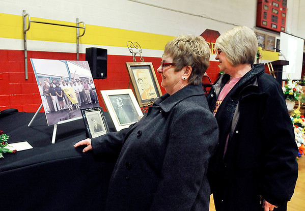 "John P. Cleary | The Herald Bulletin<br /> Cindy Jacobs and Susie Kettery look at a display of photos during visitation for Orvis ""Shorty"" Burdsull Saturday held in the Alexandria Intermediate School gym."