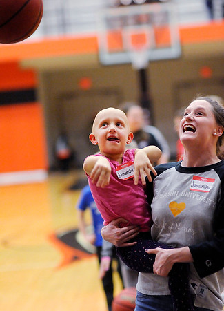 "Don Knight | The Herald Bulletin<br /> ""Team Up With Trev and Robbie""<br /> Samantha Maitz, 4, gets a lift from Anderson University student Samantha Case as she shoots a free throw during halftime of Anderson University's game against Manchester on Wednesday. AU held ""Team Up With Trev and Robbie"" for support of the Alopecia community that included dinner, admission to the game and a chance to meet AU's Trevor Lucas and Manchester's Adrian ""Robbie"" Johnson who both have Alopecia."