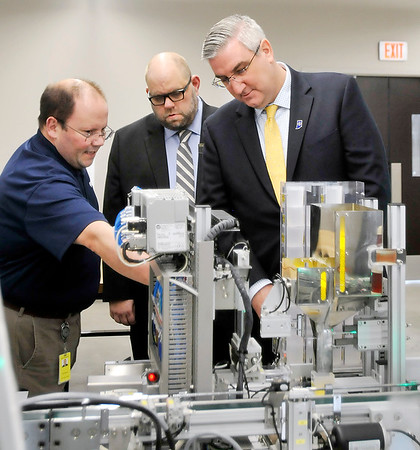 John P. Cleary | The Herald Bulletin<br /> John Wardwell, left, SMC national training manager, explains to Indiana Gov. Eric Holcomb, right, the operation of their HAS-200 Highly Automated System they have at Purdue Polytechnic for engineering students to learn on as Cory Sharp, center, director of Purdue Polytechnic, gives the governor a tour of the facility Monday.