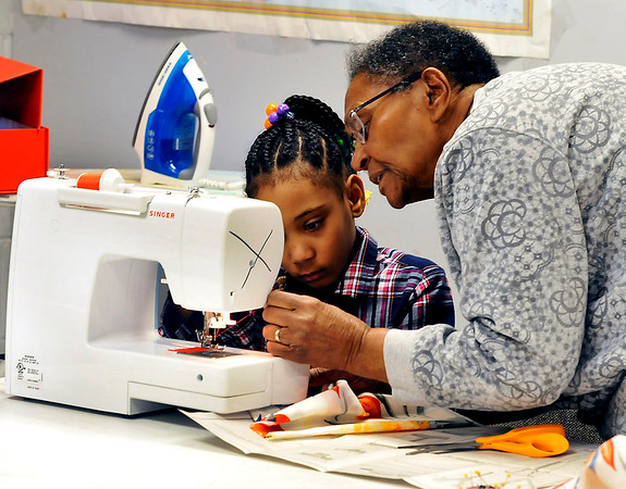 John P. Cleary | The Herald Bulletin<br /> Breonna Winburn, 8, watches closely as instructor Nora Boyd assists her in setting up her sewing machine during sewing classes at the Trustee's Boys and Girls Club in Anderson.