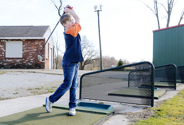 Don Knight | The Herald Bulletin<br /> Luke Bush, 14, takes advantage of the spring like weather on Tuesday and practices his swing at the Meadowbrook Golf Course driving range on Tuesday.
