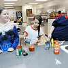 Don Knight |  The Herald Bulletin<br /> Alexis Berastegui, center, adds pepper to her sloppy joe sauce during Highland Middle School's after school cooking club. Other members of the club are Kelsey Villano, left, and Kiersten Laudill, right.