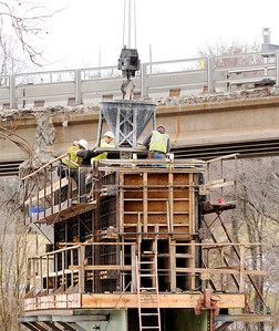 Don Knight   The Herald Bulletin Crews pour the bridge cap for pier five on the Eisenhower bridge project on Friday. Due to high water levels the concrete was delivered by crane from the east bound lane of the bridge resulting in the need to close Eighth Street for two hours.