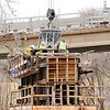 Don Knight | The Herald Bulletin<br /> Crews pour the bridge cap for pier five on the Eisenhower bridge project on Friday. Due to high water levels the concrete was delivered by crane from the east bound lane of the bridge resulting in the need to close Eighth Street for two hours.