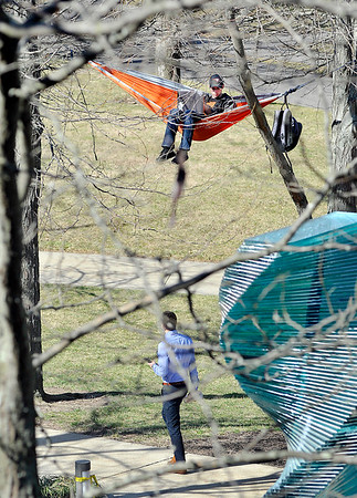 John P. Cleary | The Herald Bulletin<br /> Zachary Reid, AU freshman from Van Buren, Ind., enjoys the warm weather from his hammock high above Helios, outside of Hartung Hall Tuesday afternoon.