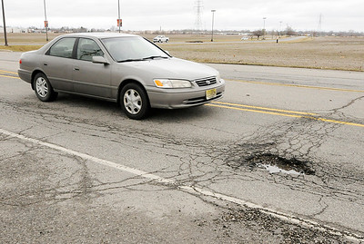 Don Knight   The Herald Bulletin A motorists avoids a pothole in the 2000 block of East 53rd Street on Friday.