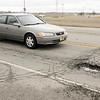 Don Knight | The Herald Bulletin<br /> A motorists avoids a pothole in the 2000 block of East 53rd Street on Friday.