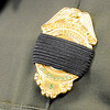 Don Knight | The Herald Bulletin<br /> Conservation officers wear a black band over their badges during the visitation for Conservation Officer Ed Bollman at Madison Park Church of God on Friday.