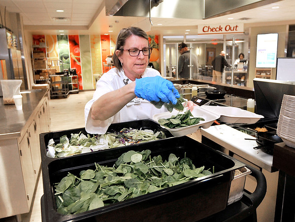 John P. Cleary | The Herald Bulletin<br /> Debbie Trimble puts down a bed of spinach for the sizzling salad she is making Wednesday in Community Hospital's Café 15fifteen.