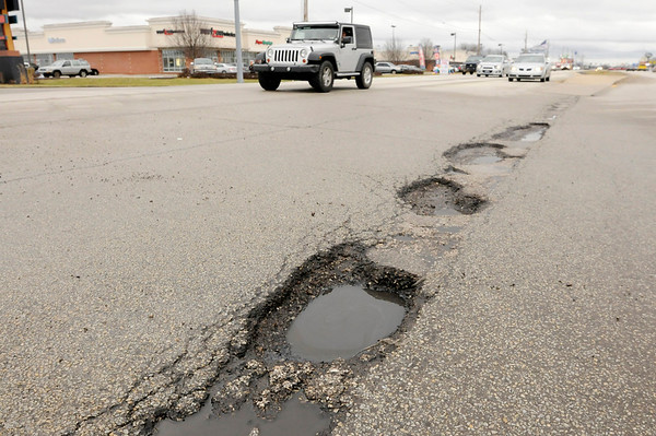 Don Knight | The Herald Bulletin<br /> Motorists pass several potholes at the intersection of Scatterfield and Charles Street on Friday.