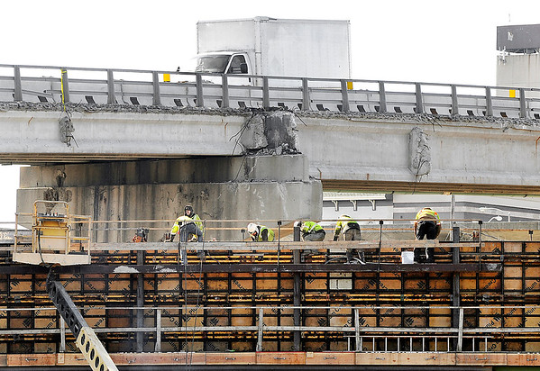 John P. Cleary | The Herald Bulletin<br /> As traffic goes over the eastbound lane of Eisenhower Bridge Friday these workers finish the forms of one of the new horizontal bridge supports for the westbound lanes of the new bridge construction.