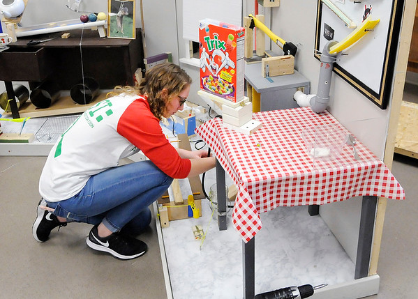 Don Knight | The Herald Bulletin<br /> Dakotah Alumbaugh, 16, prepares a packet of baking soda to fall into vinegar filling a balloon with gas and pouring a bowl of cereal in the last of 73 steps in Anderson High School's Rube Goldberg machine.