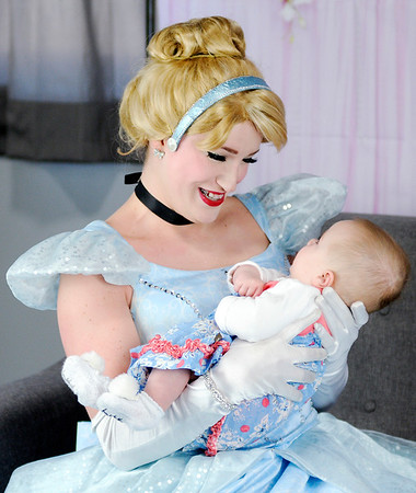 Don Knight | The Herald Bulletin<br /> Haley Geiger dressed as Cinderella holds four-month-old Aria Wilson at Aerial Fit2Fly on Saturday. Geiger is owner of Royal Wishes.