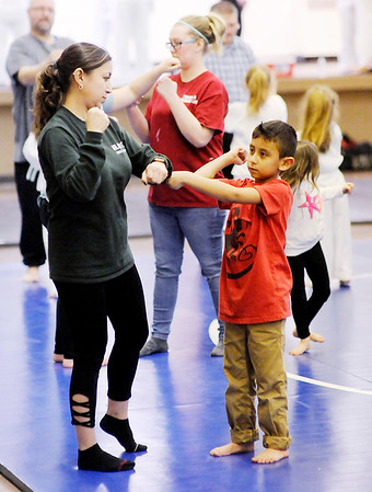 Don Knight | The Herald Bulletin<br /> Ericka Ortiz and her son Eduardo Lopez, 7, practice moves lay learned during a free children's safety program at the Mill Creek Civic Center on Wednesday.