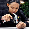 John P. Cleary | The Herald Bulletin<br /> Six-grader COMPASS student Erica Murdock strikes her letter punch with a hammer as she makes her My Intent bracelet.