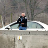 John P. Cleary | The Herald Bulletin<br /> This Indiana State Trooper keeps an eye on oncoming traffic as he assists this motorist with a flat tire on I-69 northbound just north of the 226 mile marker Wednesday afternoon. There were numerous flat tires caused by potholes along the interstate Wednesday.