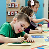 John P. Cleary | The Herald Bulletin<br /> Mason Johnson, 5, concentrates as he works on his sandpaper & crayons art piece Monday afternoon at the Anderson Public Library. Mason was taking part in a Art Adventures program in the Children's Department making crayon artwork on sheets of sandpaper.