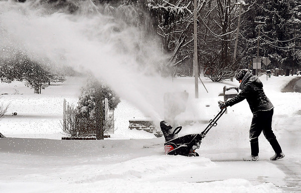 John P. Cleary   The Herald Bulletin<br /> Norma Rakes kicks up a big plume of snow as she cleans off her driveway along Mounds Road Friday morning after about five inches of snow fell overnight.
