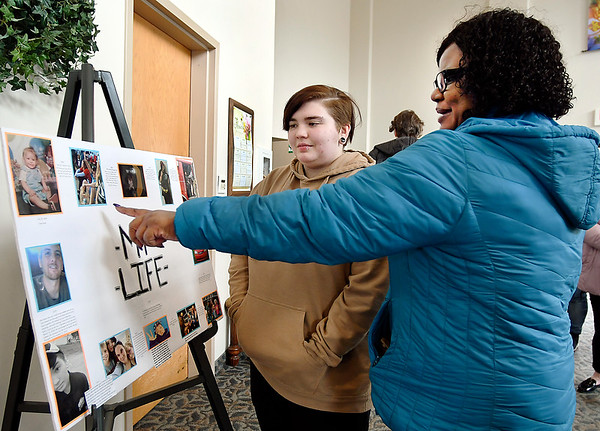 John P. Cleary | The Herald Bulletin Cameron Shepard, a senior at the Carnegie Learning Center, and Arnetta Peak discuss Shepard's PhotoVoice display during the Carnegie Learning Center's PhotoVoice Gallery event held Thursday at the First United Methodist Church in Pendleton.