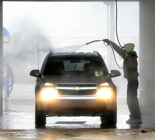 John P. Cleary | The Herald Bulletin<br /> With the warmer temperatures and snowmelt, this driver gets the road grime off his vehicle Tuesday afternoon at The Wash Tub on north Broadway just in time for rain to move in overnight.