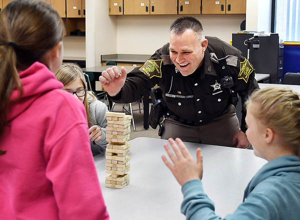 John P. Cleary   The Herald Bulletin<br /> Madison County Sheriff's DARE officer Darren Dyer plays Jenga with these Maple Ridge Elementary School fifth-graders during their indoor recess this past week.