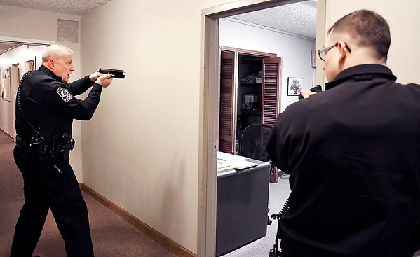 John P. Cleary   The Herald Bulletin<br /> Edgewood police officer Shane Briggs and Lapel police officer Timothy Petty work together to check and clear this room in Lone Oak Wesleyan Church of a possible gunman during an active shooter training session Monday evening at the church. This was an cooperative training session for both the Lapel and Edgewood police and fire departments.