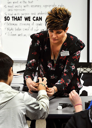 John P. Cleary   The Herald Bulletin<br /> Kristal McCorkle, COMPASS director, assists a student on putting their My Intent bracelets on their wrist after they have finished putting their word of focus on their bracelet.