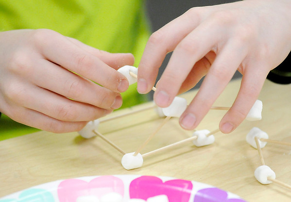 Don Knight | The Herald Bulletin Clayton Rainey makes a house for Cupid out of toothpicks and marshmallows at Summitville Elementary on Thursday.
