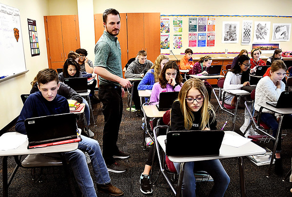 John P. Cleary | The Herald Bulletin<br /> Pendleton Heights Middle School math teacher Darin DeNeal checks on the progress of his seventh-grade students as they work their math problems in class recently.