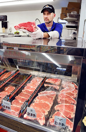 John P. Cleary | The Herald Bulletin<br /> Harvest Market was voted Best Grocery Store Meat Department.<br /> Chris Weir, meat manager of the Harvest Market at 8th & Scatterfield in Anderson, shows a T-Bone steak to a customer.