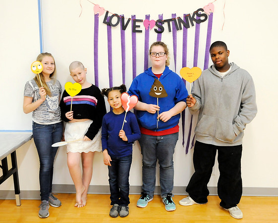 Don Knight   The Herald Bulletin<br /> From left, Gracie Bolton, Alexis Fullmer, Jaslynn Hix, Laura McCarty and Trey Banks pose for photo in a photo booth set up for an Anti-Valentine's Day Party for teens at the Anderson Public Library on Saturday.