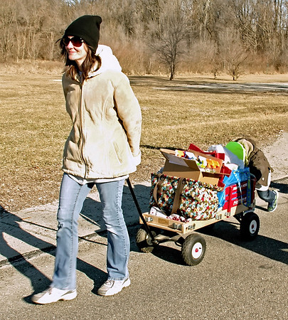 "Mark Maynard | The Herald Bulletin<br /> With a little help from her son Roland, Amanda Capes pulls a wagon-load of supplies to the Anderson Christian Center during the annual ""Walk a MIle in My Shoes"" fundraiser on Saturday morning."