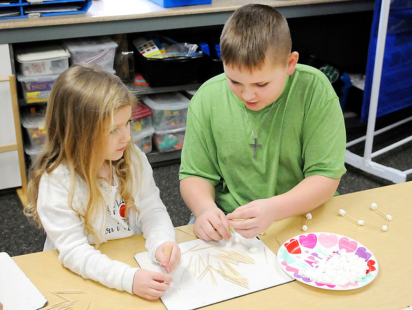 Don Knight | The Herald Bulletin From left, kindergarten student Elsy Mann and fourth grader Cooper Rudy uses toothpicks and marshmallows to create a home for Cupid at Summitville Elementary students on Thursday. Students from Samantha Smith's kindergarten class and Kandi Pretorius' fourth grade class are teamed up and come together once a week.