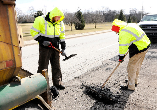 Don Knight | The Herald Bulletin<br /> From left, Remington Emery and Pat McKenzie patch potholes on Raible Avenue on Friday.