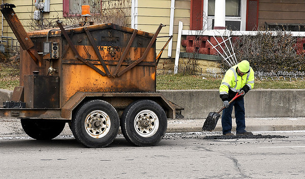 John P. Cleary | The Herald Bulletin<br /> Anderson city workers patching potholes along Brown-Delaware<br /> Street Friday.