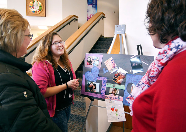 John P. Cleary | The Herald Bulletin<br /> Meghan Ruiz, center, a Carnegie Learning Center sophomore, explains her PhotoVoice display to guests during the Carnegie Learning Center's PhotoVoice Gallery event held Thursday at the First United Methodist Church in Pendleton.