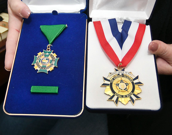 Belinda Bollman shows the two Medals of Honor her late husband, Indiana Conservation Officer Sgt. Ed Bollman, received from the State of Indiana and the Indiana FOP for his actions in attempting to save a friend while ice fishing. The accident claimed both their lives a year ago.