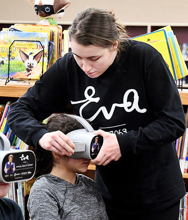 Jessica Chapman, Eva Project Distribution & Impact Manager for WFYI Indianapolis, helps a student adjust their virtual reality headset for the Eva Kor Experience.